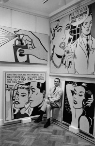 Roy Lichtenstein at Castelli Gallery sitting with Spray (1962), Masterpiece (1962), Engagement Ring (1961) and Aloha (1962), 1962. Photograph by Bill Ray